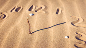 Clock dial in sand. Clock dial made of sand, twigs and shells Royalty Free Stock Images