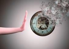 Clock disintegrating, resisting the passage of time. Hand preventing the clock from disintegrating, resisting against the passage of time stock photos