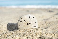 Clock drawn on a stone, on the sand of a beach royalty free stock photography