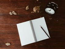 Clock, dry leaves, notebook and pencil on wooden table Stock Image