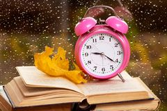 Clock and dry maple leaf on a book against the background of the window in the rainy weather in the fall of the evening. Reading royalty free stock photography