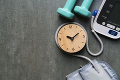 Clock, dumbbell and blood pressure monitor on the ta Royalty Free Stock Photos
