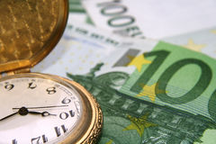 Clock on euros. Old hand watch on euro bills stock photography