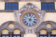 Clock on facade of ancient palace over the square of San Michele in Foro in Lucca, Italy Stock Photography