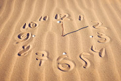 Clock face  on beach. Illustration of a clock face with hands pointing to 12 and 2 created on a sandy beach covered in a feint ripple pattern Stock Photography
