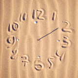 Clock face  on beach. Illustration of a clock face with hands pointing to 12 and 2 created on a sandy beach covered in a feint ripple pattern Stock Photo