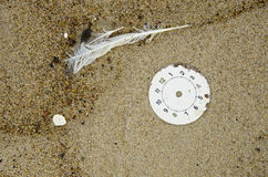 Clock face on beach sand and feather Royalty Free Stock Images
