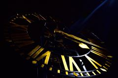 Clock face with golden spades shape hour hand and roman numerals royalty free stock images