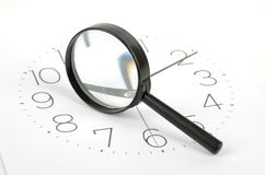 Clock face and magnifier Stock Photography