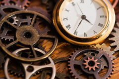 Clock and Old Gears. A clock face and old gears on a wooden surface Royalty Free Stock Photos