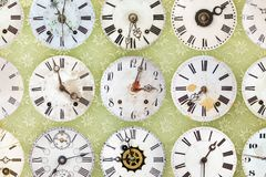 Clock faces in front of retro wallpaper Stock Photo