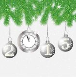 Clock and festive marbles with numbers 2015 hang on the branches Stock Photos