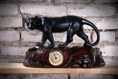 Clock with figurine of panther. Vintage wooden carved clock with figurine of panther Stock Photo
