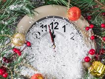 Clock with fir branches and Christmas decorations in the snow Stock Photos