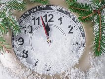 Clock on snow under decorated christmas tree stock photo