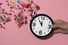 Clock at five to twelve and confetti. Confetti of different colors falling over a clock at five to twelve in the hand of a young man, against a pink background Stock Photo