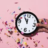 Clock at five to twelve and confetti. Confetti of different colors falling over a clock at five to twelve in the hand of a young man, against a pink background Stock Image
