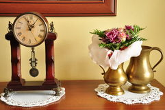 Clock, flowers and  vases. Stylish clock on the dresser and jug with flowers Stock Photos