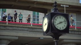 Clock in foreground with commuters waiting on a train station stock video