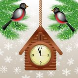 Clock in form house and bullfinchs on green branches Stock Photo