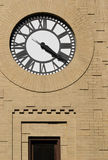 Clock with Freestyle Masonry Surround. Tower clock with Roman numerals and a freestyle, relieved yellow-brick masonry surround in Columbia, Pennsylvania USA royalty free stock image