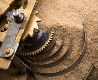 Clock gears in sand. Mechanical endurance - clock gears in sand royalty free stock images