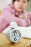 Clock with girl in class room Royalty Free Stock Image