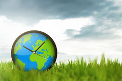 Clock of globe on the meadow Royalty Free Stock Image