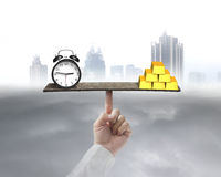 Clock and gold balancing on seesaw supported by finger Stock Image