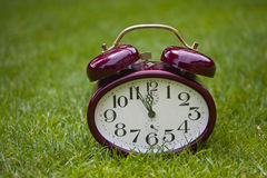 Clock on a grass Stock Images