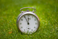 Clock on a grass Royalty Free Stock Photography