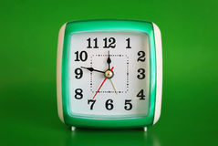 Clock on green background Stock Photos