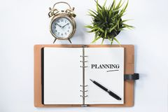 Clock, green plant and blank notebook with PLANNING word stock image