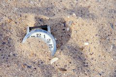 The clock is half buried in the sand on the beach. Stock Photography