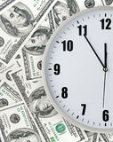Clock with hand on money background Stock Image