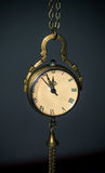 A clock hanging on the chain. An old clock hanging on the chain Royalty Free Stock Image