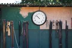 Clock hanging on wall. Clock hanging on half-painted wall shows eight minutes to eleven o`clock Royalty Free Stock Images