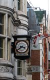 A clock hanging from the side of a building royalty free stock photo