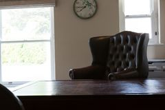 Clock hanging on wall with arm chair in living room Royalty Free Stock Photography