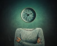 Clock headed. Surreal image of a confident woman with crossed hands and a clock instead of head over blackboard background. The concept of time in educational Royalty Free Stock Images