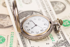 Clock on a heap of paper dollars Stock Image