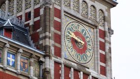 The clock on the historic building in Amsterdam, from different angles. Clock tower, detail, craftsmanship and art, red clock Stock Photography