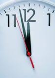 Clock hitting 12 O'clock Stock Photo
