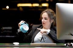 clock holding woman Kvinnan rymmer en ringklocka i hennes hand i arbetsplatsen royaltyfria bilder