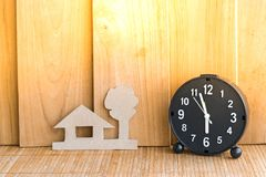 Clock with home paper shape on wood board background.using wallpaper for education, business photo.Take note of the product for bo Stock Photo