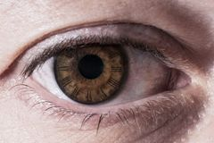 Clock in human eye, passing time concept image. A clock inside an human eye, concept for the passing time stock image