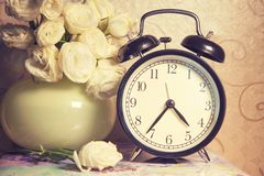 Clock ikebana and vintage on table. Vintage retro clock and ikebana on table stock photography