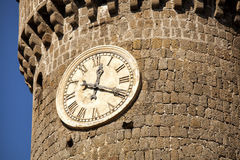 Clock italian tower of the village of Bagnaia. Italy. A big tower of a castle with a clock with roman numerals. Bagnaia (little italian village) is a fraction of stock photos