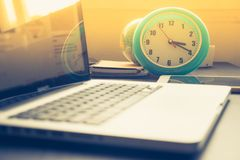 Clock with Laptop on office desk and  sunshine in afternoon. Clock with Laptop on office desk and Stock Photography