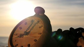 Clock left at sunset near sea shore zooming time lapse stock footage